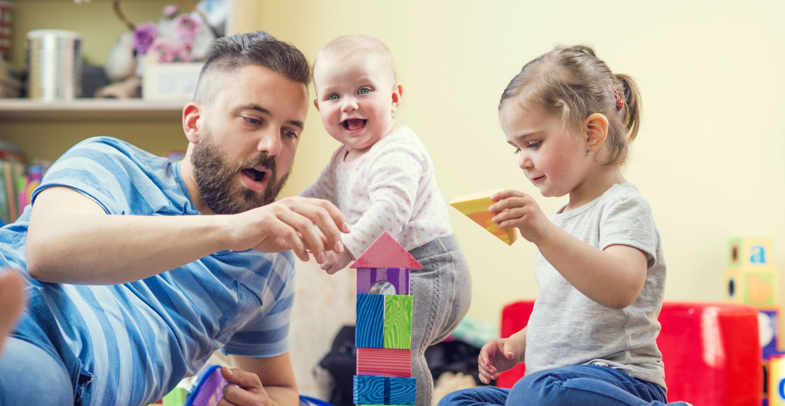Father Building Block House with Infant and Toddler